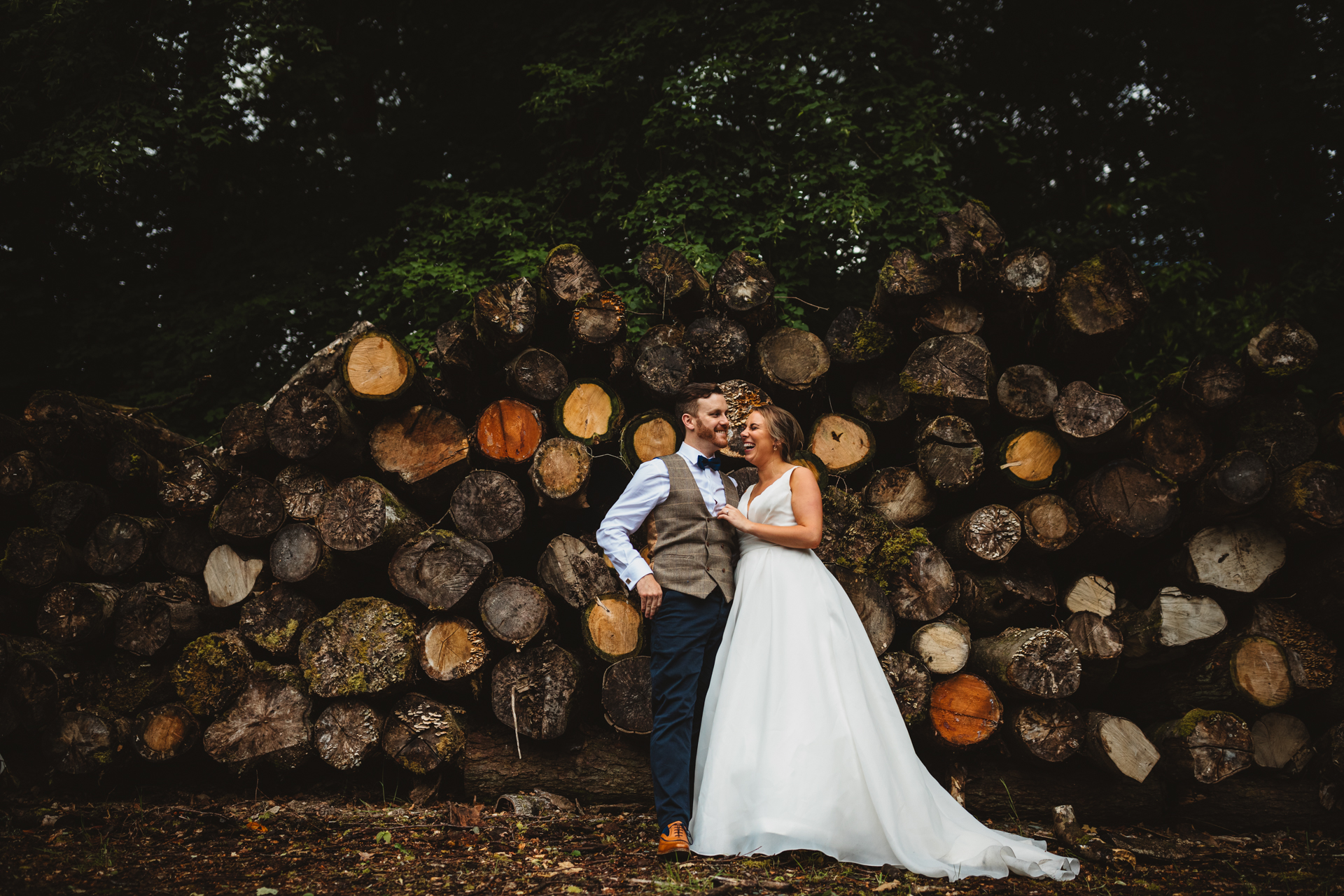 Bride & Groom laughing stood in front of a pile of logs