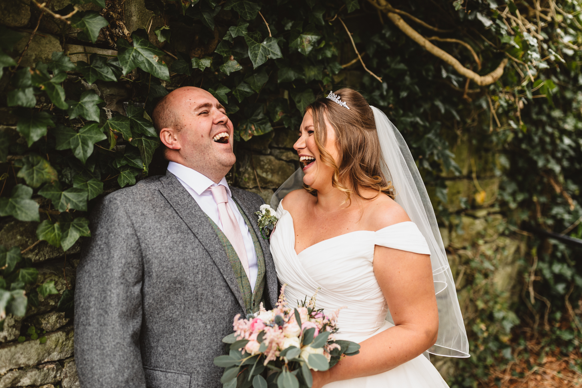 bride and groom laughing in front of an ivy wall