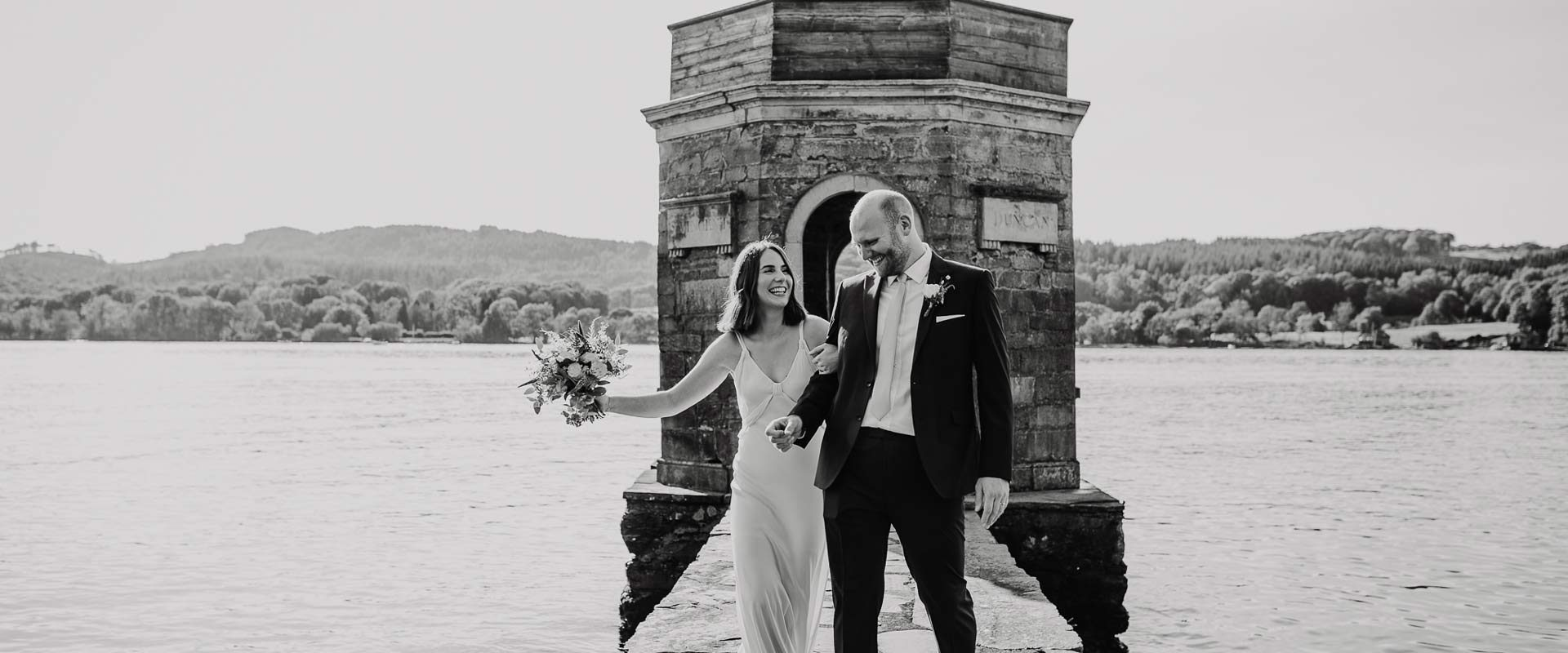 black and white picture of a bride and groom laughing on a pier on a lake